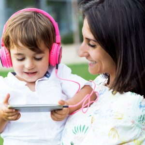 Portrait of beautiful young mother with her son listening to music in the park.