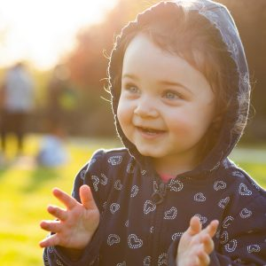 Little baby girl plays happy in the park outdoors in the spring in backlight.